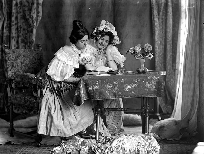 Mise en scène de modèles féminins, intérieur : deux jeunes femmes, habillées à la manière du style Louis-Philippe, assise à une table, lisant