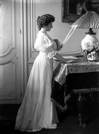 Mise en scène d'un modèle féminin, intérieur : jeune femme, vue de profil, debout à côté d'une table, lisant