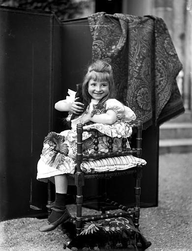 Portrait d'une fillette assise dans un fauteuil, tenant des chatons dans ses bras, vue de trois-quart face