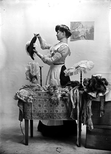 Mise en scène d'un modèle féminin, intérieur : jeune femme (modiste), vue de profil, debout à côté d'une table, arrangeant un chapeau
