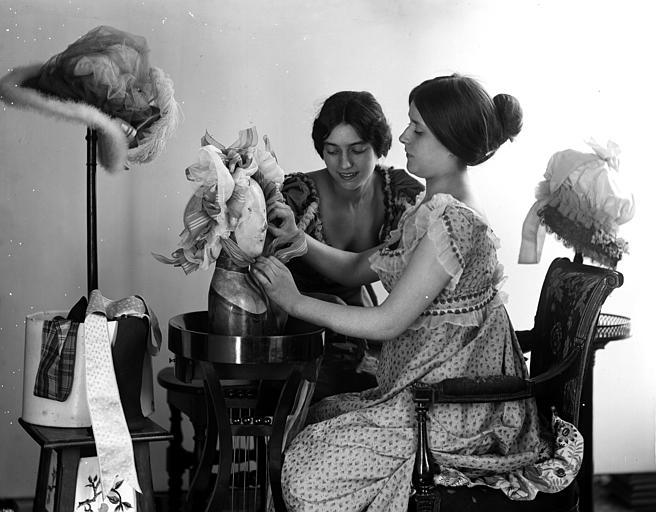 Mise en scène de modèles féminins, intérieur : deux jeunes femmes (modistes), assises à une table, arrangeant un chapeau