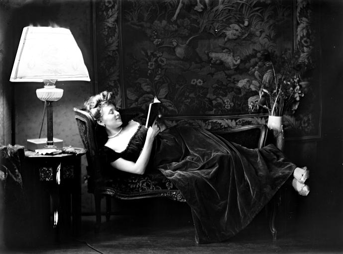 Mise en scène d'un modèle féminin, intérieur : jeune femme allongée sur un canapé, lisant