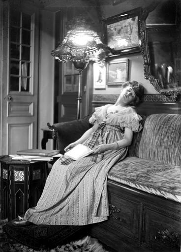 Mise en scène d'un modèle féminin, intérieur : jeune femme assoupie dans un canapé, son livre à la main