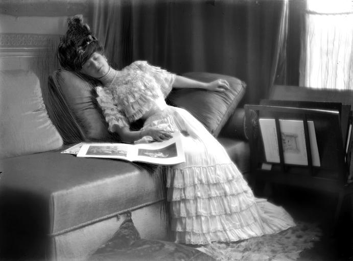 Mise en scène d'un modèle féminin, intérieur : jeune femme avec un chapeau assoupie dans un canapé, son livre à côté d'elle