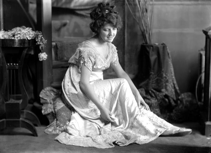 Mise en scène d'un modèle féminin, intérieur : jeune femme assise au bas d'un escalier