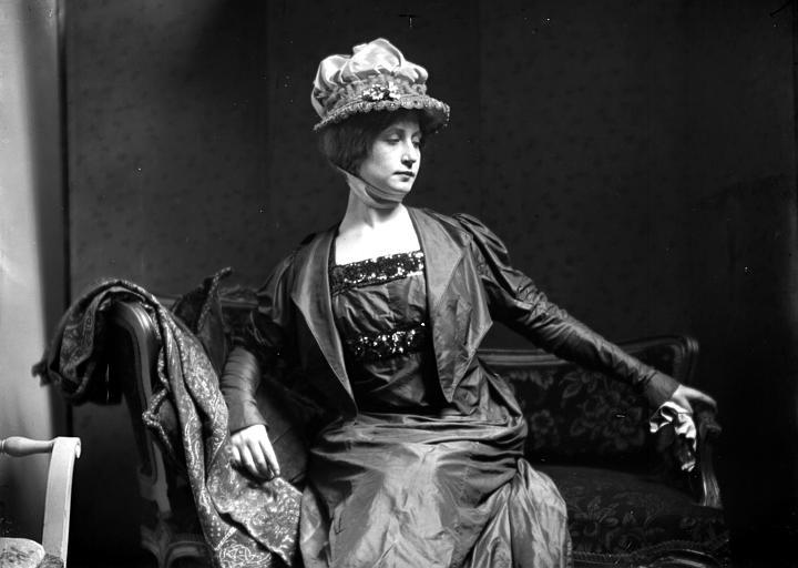 Mise en scène d'un modèle féminin, intérieur : jeune femme assise, portant chapeau et une petite veste, posant dans un large fauteuil