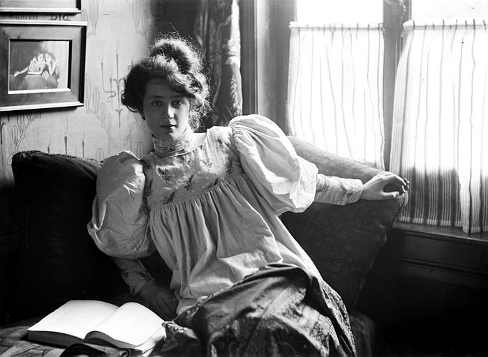 Mise en scène d'un modèle féminin, intérieur : jeune femme portant une blouse, assise dans un canapé, à côté d'une fenêtre, son livre posé à côté d'elle. Au mur photographie encadrée de Constant Puyo