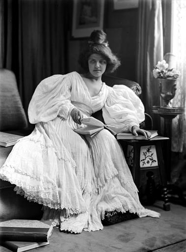 Mise en scène d'un modèle féminin, intérieur : jeune femme assise avec un livre sur les genoux, vue de face