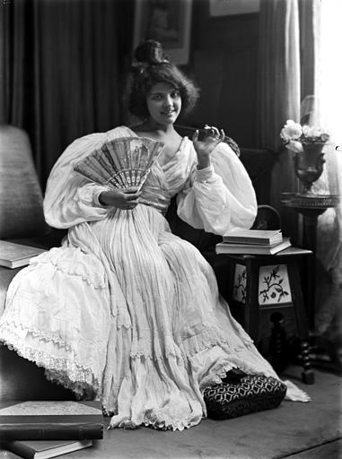 Mise en scène d'un modèle féminin, intérieur : jeune femme assise avec un éventail ouvert sur sa poitrine, vue de face