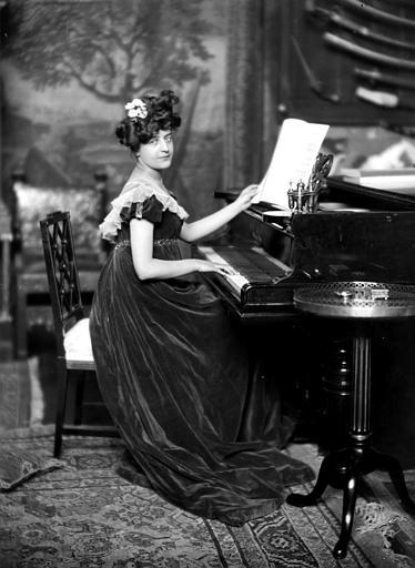 Mise en scène d'un modèle féminin, intérieur : femme assise au piano, habillé en style empire