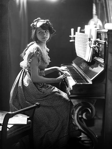 Mise en scène d'un modèle féminin, intérieur : jeune fille assise, jouant du piano