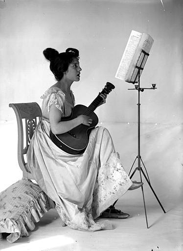 Mise en scène d'un modèle féminin, intérieur : jeune femme assise, jouant de la guitare, vue de profil