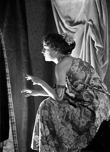 Mise en scène d'un modèle féminin, intérieur : jeune femme assise, vue de profil avec un effet de lumière