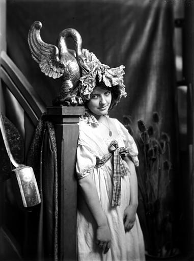 Mise en scène d'un modèle féminin, intérieur : jeune fille accôtée à une rampe décorée d'une statue de cygne