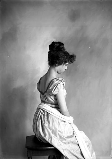 Mise en scène d'un modèle féminin, intérieur : jeune fille assise, cheveux relevés en chignon, vue de trois-quarts dos