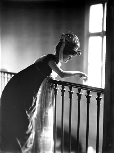 Mise en scène d'un modèle féminin, intérieur : femme s'appuyant à une rampe de cage d'escalier, effet de contrejour