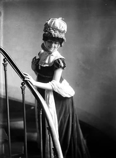 Mise en scène d'un modèle féminin, intérieur : femme dans un escalier, habillée en style empire, regardant vers le bas