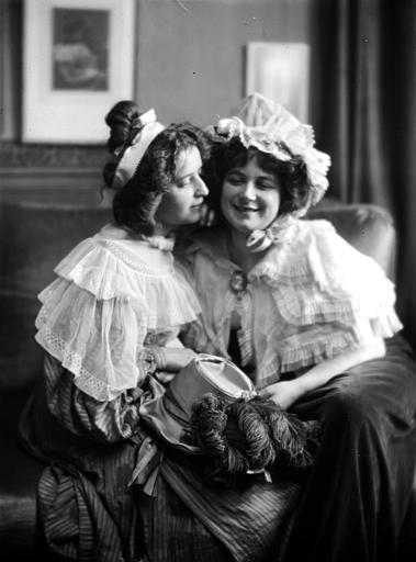 Mise en scène d'un modèle féminin, intérieur : deux jeunes femmes assises sur un canapé, conversant 'joue contre joue', habillées en style Louis-Philippe