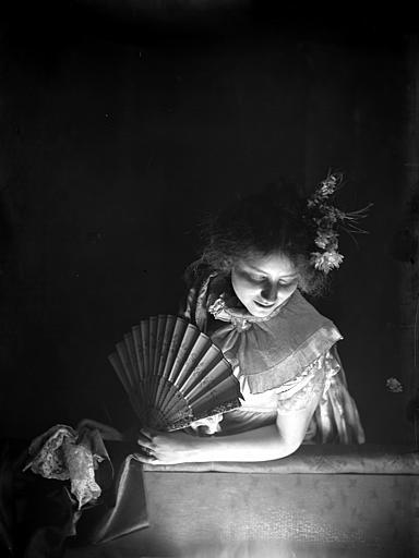 Mise en scène d'un modèle féminin, intérieur : jeune fille accoudée avec un éventail dans la main, regardant vers le bas, effet de lumière