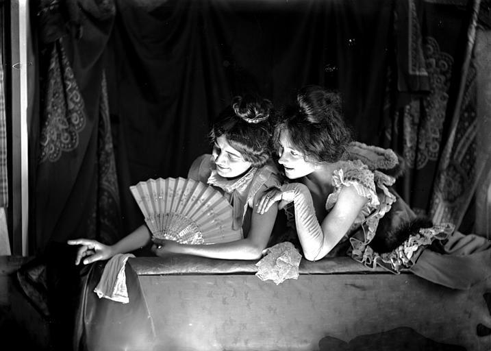 Mise en scène d'un modèle féminin, intérieur : deux jeunes filles accoudées avec un éventail dans la main, regardant vers le bas, effet de lumière
