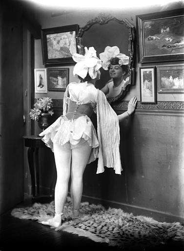 Mise en scène d'un modèle féminin, intérieur : jeune femme se regardant dans un miroir, habillée avec un justaucorps. Au mur photographies encadrées de Constant Puyo