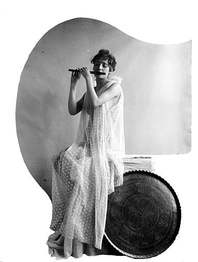 Mise en scène d'un modèle féminin, intérieur : jeune femme avec une toge en organdi transparent, jouant du fifre