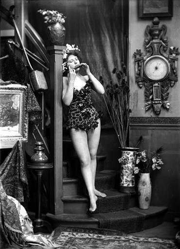 Mise en scène d'un modèle féminin, intérieur : jeune femme en justaucorps jouant du fifre, posant au bas d'un excalier