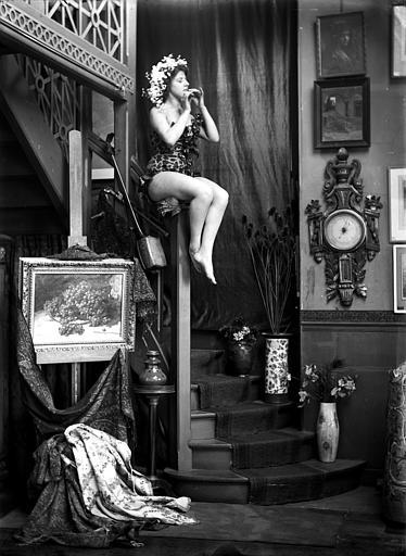 Mise en scène d'un modèle féminin, intérieur : jeune femme en justaucorps jouant du fifre, assise sur le haut de la rampe d'escalier