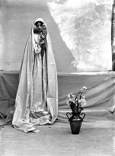 Mise en scène extérieure : jeune femme habillée (évocation naturaliste, mouvement pictorialiste) d'une robe blanche portant un voile sur ses cheveux, en pied, vue de face, à côté d'un vase de fleurs