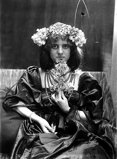 Portrait de jeune femme, portant un chapeau en sequins et fleurs, assise, tenant une fleur à la main, de face