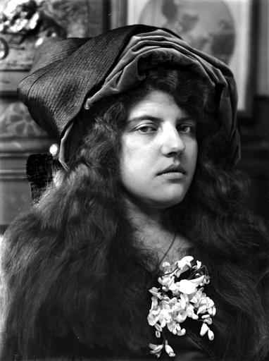 Portrait de jeune femme avec les cheveux libres, portant un chapeau, fleurs au décolleté, vue de trois-quarts face
