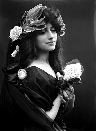 Portrait d'une jeune femme, portant une coiffure en plume et fleurs, camée sur l'épaule, vue de trois-quarts face