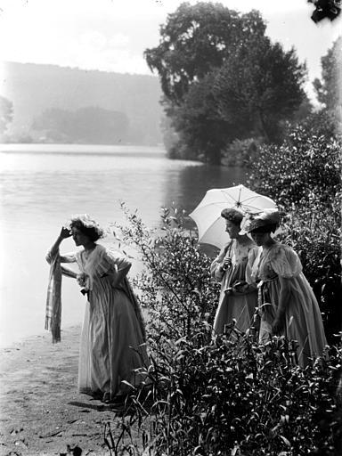 Mise en scène extérieure : trois jeunes femmes avec ombrelle posant près de l'eau, effet de mouvement