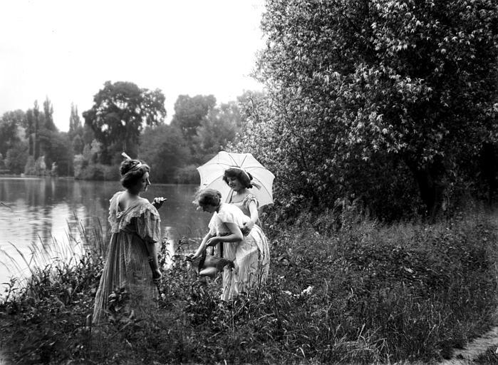 Mise en scène extérieure : trois jeunes femmes avec ombrelle posant près de l'eau