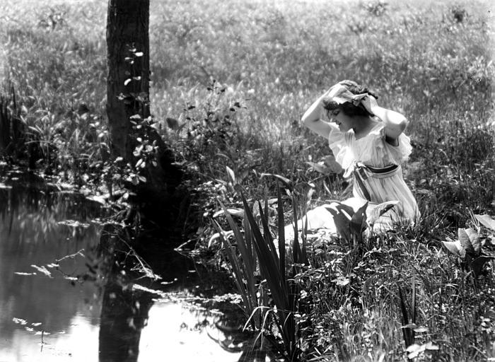 Mise en scène extérieure : jeune femme se recoiffant au bord de l'eau
