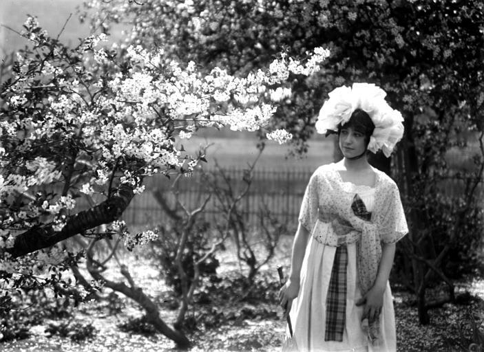 Mise en scène extérieure : jeune femme posant au milieu de la nature, portant un châle et un chapeau, regardant un arbre en fleurs, vue de trois-quarts face