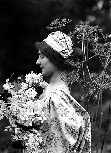 Mise en scène extérieure : jeune femme posant au milieu de fleurs sauvages, vue de profil