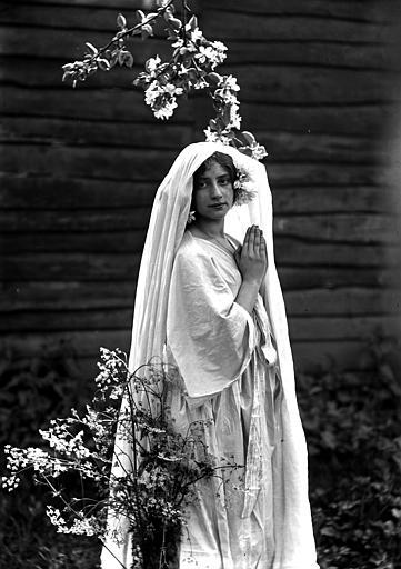 Mise en scène extérieure : jeune femme habillée (évocation naturaliste, mouvement pictorialiste) d'une robe blanche portant un voile sur ses cheveux, posant au mileu de la nature, les mains en prière