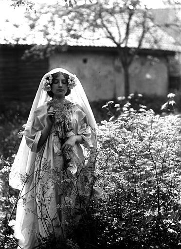 Mise en scène extérieure : jeune femme habillée (évocation naturaliste, mouvement pictorialiste) d'une robe blanche portant un voile sur ses cheveux, posant au mileu de la nature, tenant des fleurs sauvages dans les mains