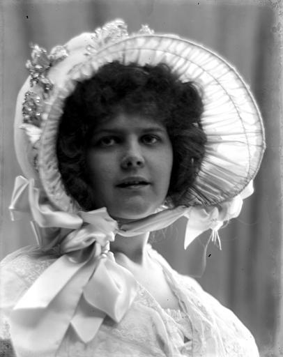 Portrait d'une jeune fille, habillée en style Louis-Philippe, portant chapeau, vue de trois-quarts face
