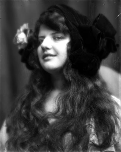 Portrait d'une jeune fille aux cheveux libres, portant un chapeau, vue de trois-quarts face