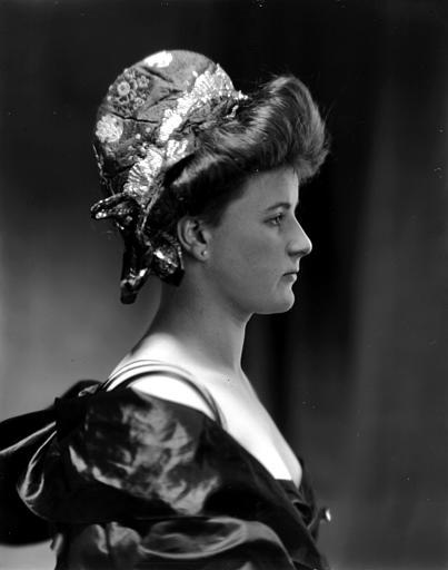Portrait d'une jeune femme portant un chapeau et une robe décolletée, vue de profil