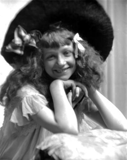 Portrait d'une fillette portant chapeau, accoudée à une table, mains posées sous le menton