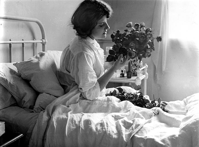 Mise en scène d'un modèle féminin, reconstitution d'une chambre d'hôpital : jeune femme assise dans son lit, tenant un bouquet dans les mains
