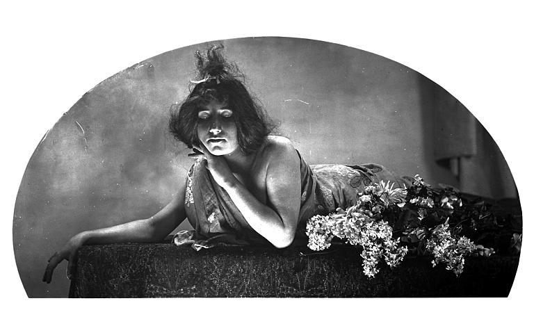 Mise en scène d'un modèle féminin : jeune femme allongée, avec un effet de lumière sur son visage