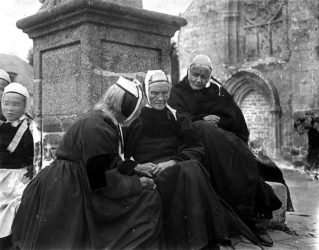Trois femmes agées en costume traditionnel assises au pied d'un calvaire