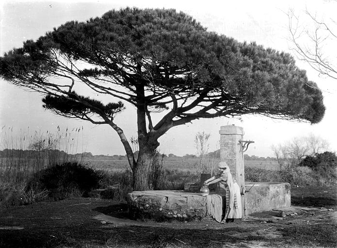 Mise en scène extérieure, paysage : jeune femme avec une cruche près d'une fontaine