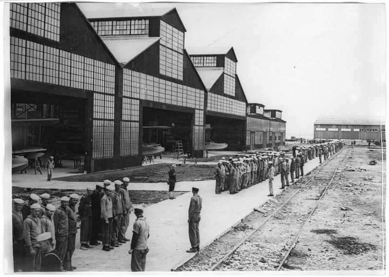 A l'heure des repas, marins américains rassemblés devant les hangars abritant des hydravions Curtis