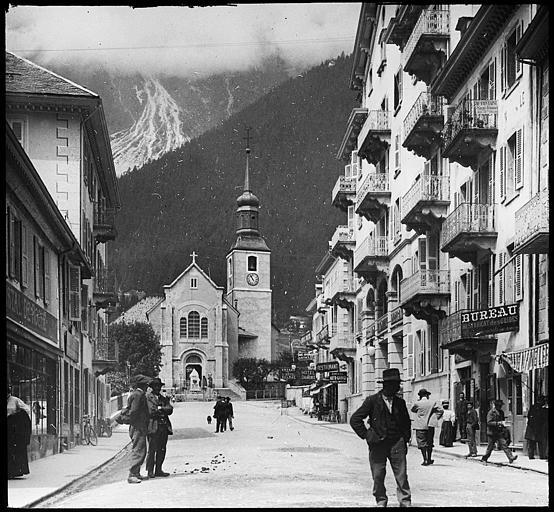 Le portail principal et le clocher ; nombreux personnages dans la rue