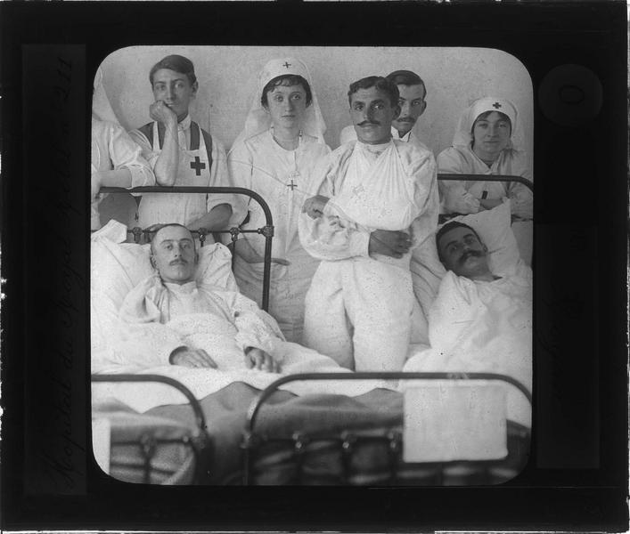 Intérieur : portrait d'infirmières et assistant de la Croix-Rouge posant à côté de malades